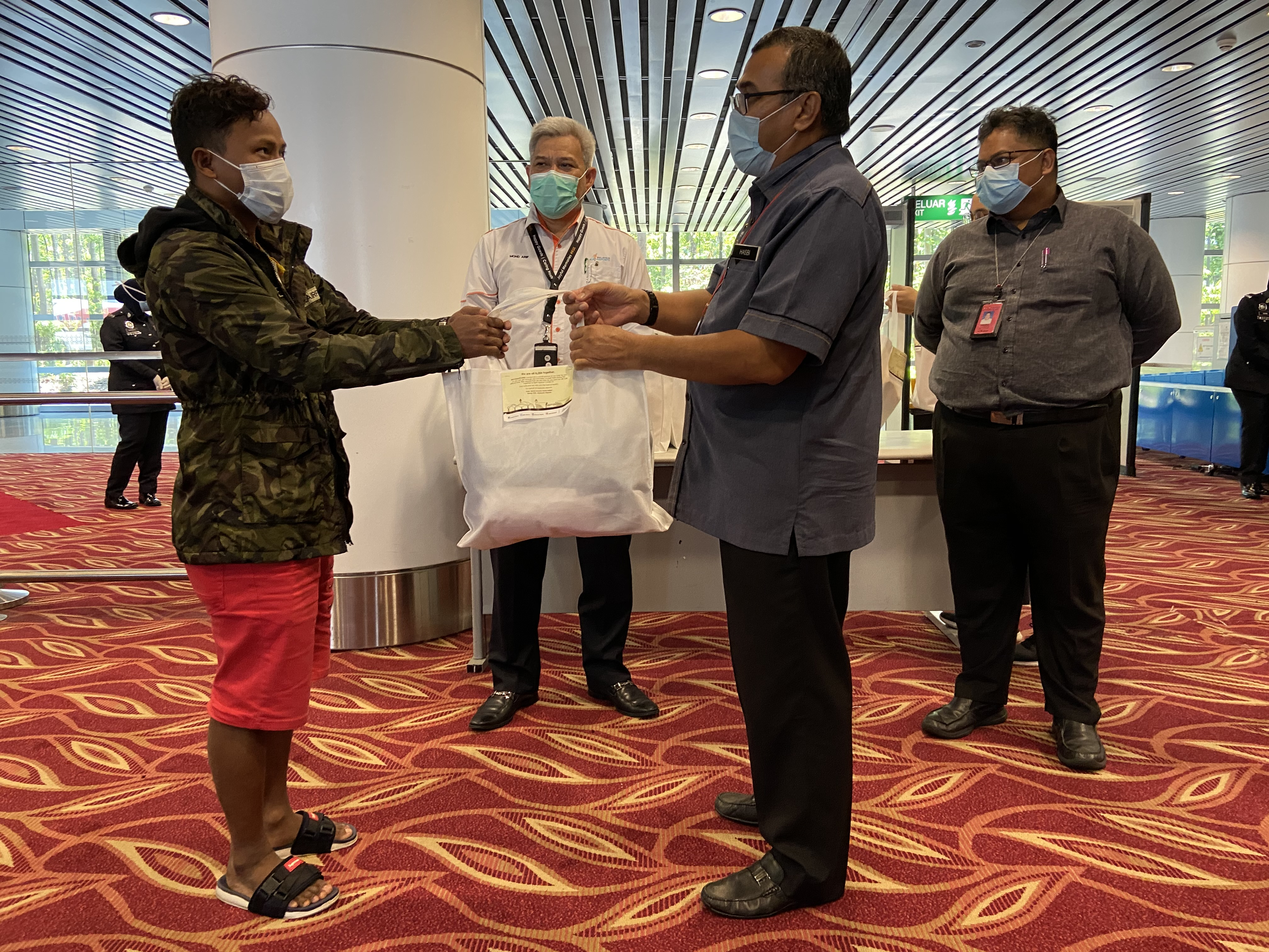 A stranded passenger receiving a comfort kit from Hasbi Habibollah, Deputy Minister of Transport Malaysia during his visit to KL International Airport (KLIA) recently.